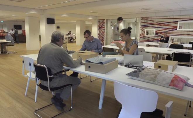Studiezaal van het Nationaal Archief met op de achtergrond het 'leslokaal'. Foto: website van het Nationaal Archief.
